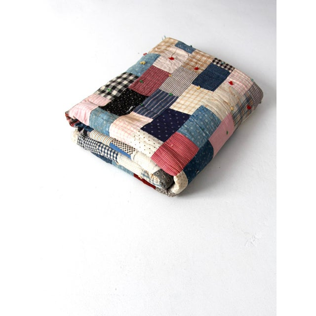 A vintage hand-tied quilt. The patchwork quilt features a square pattern in primarily blue and red cotton. The back is...