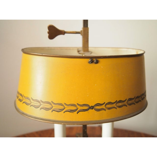 Italian Brass and Tole Bouillotte Lamp in the form of a chamber stick. Oval mustard painted tole shade with gold painted...