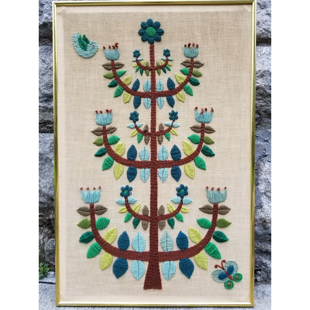 Mid 20th century modern Crewel embroidery tree , bird and butterfly motif with a brass brass frame and linen tapestry....