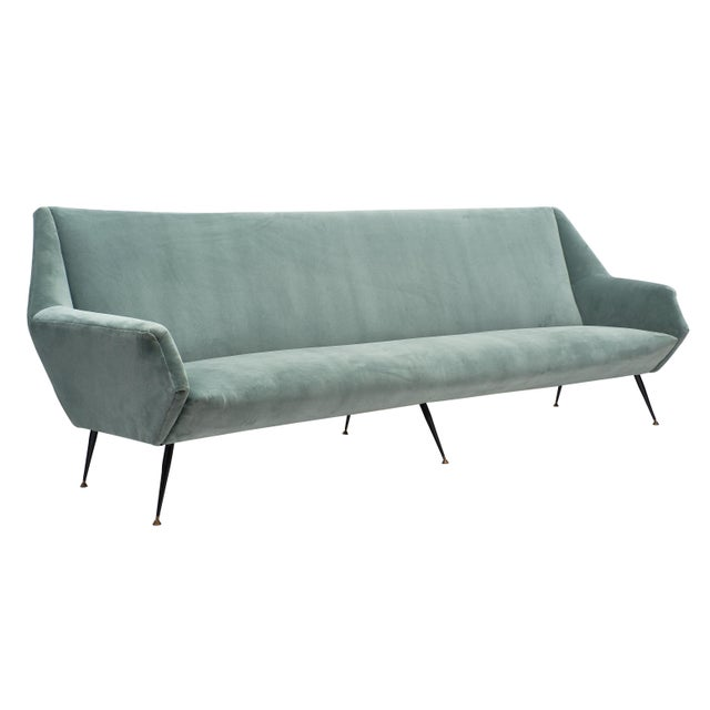An important Italian mid-century sofa, newly upholstered in an aqua velvet blend with its original black lacquered and...