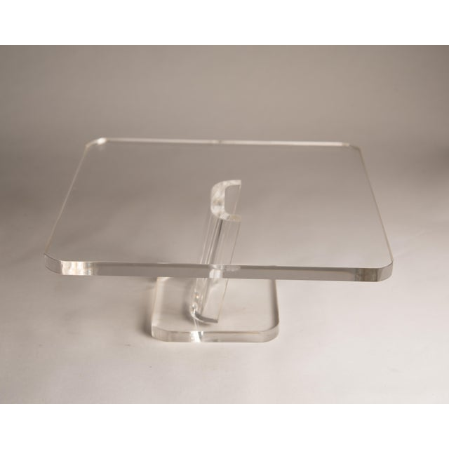 "This is a vintage lucite stand from the 1970s. The piece stands on a pedestal and is held together by an angled ""U"" shaped..."