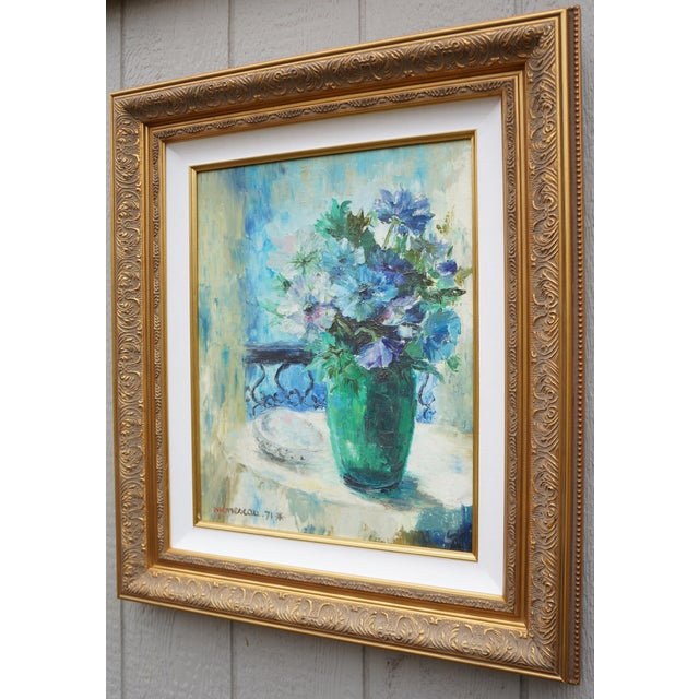 This is a strikingly beautiful still life oil painting of flowers in a shapely glass vase sitting atop a French cafe style...