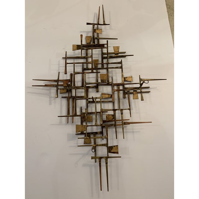 A one of a kind sophisticated hand forged mid century modern brass wall sculpture having geometric overlapping lines and...