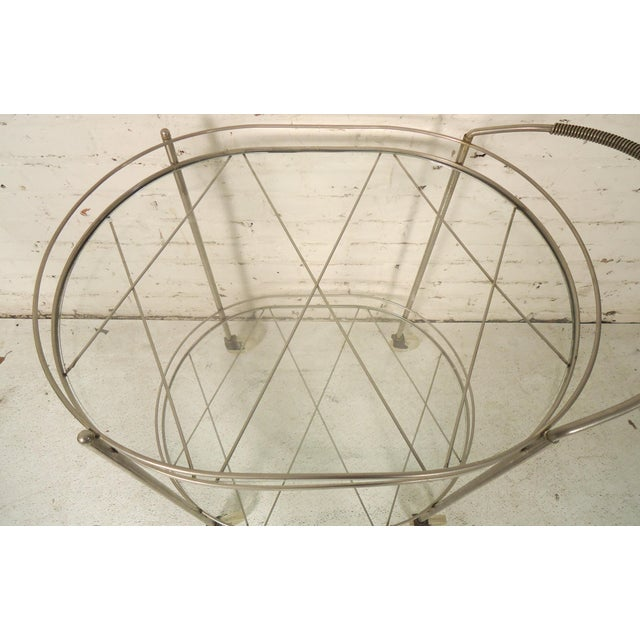 This is a great vintage style bar cart with two glass shelves set on criss-cross metal. (Please confirm item location - NY...