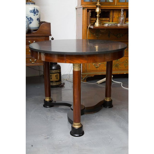 This sophisticated circular French Empire mahogany center table has a dark gray marble top over a simple frieze supported...