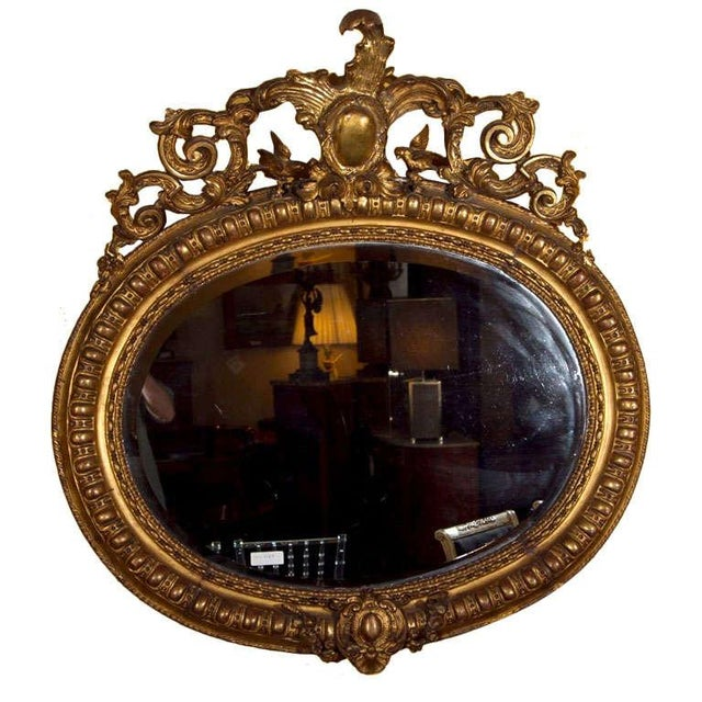 A French giltwood mirror, possibly early 20th century. The oval annular frame centered by ornately carved crest of...