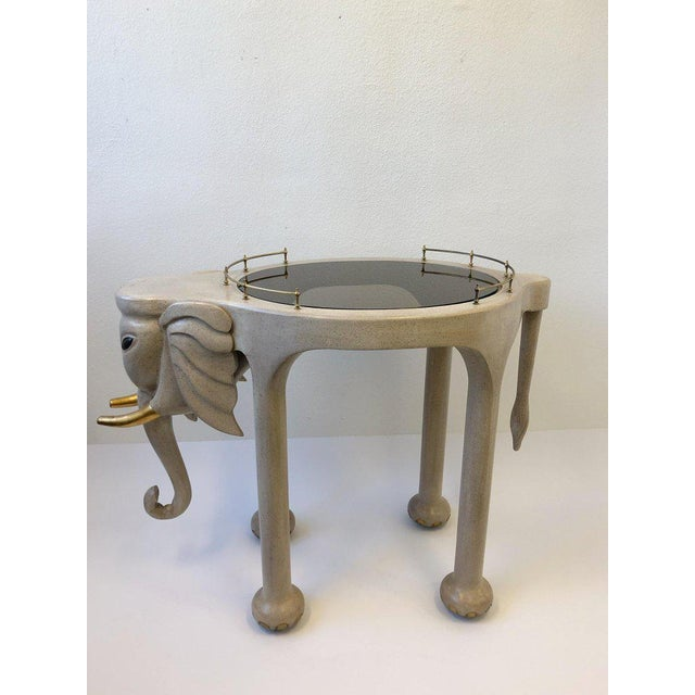 A spectacular 1980s carved wood elephant bar cart on casters by Marge Carson. The elephant is lacquered off white and gold...
