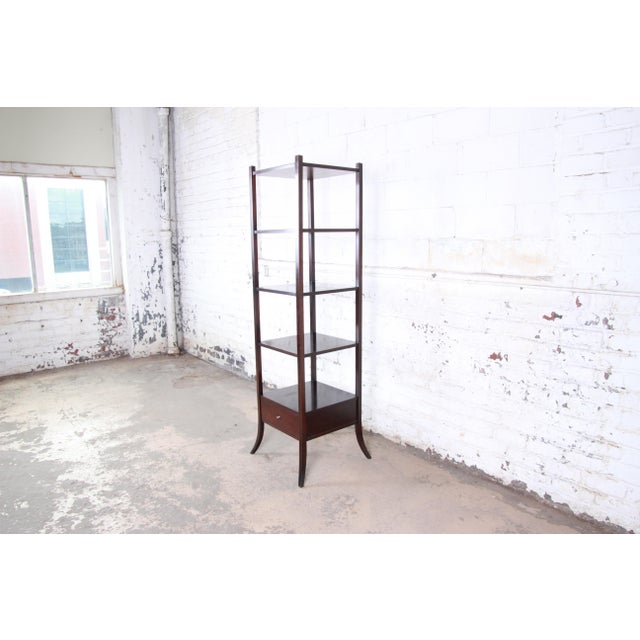 A beautiful dark mahogany etagere designed by Barbara Barry for Baker Furniture. The etagere features clean, simple lines...