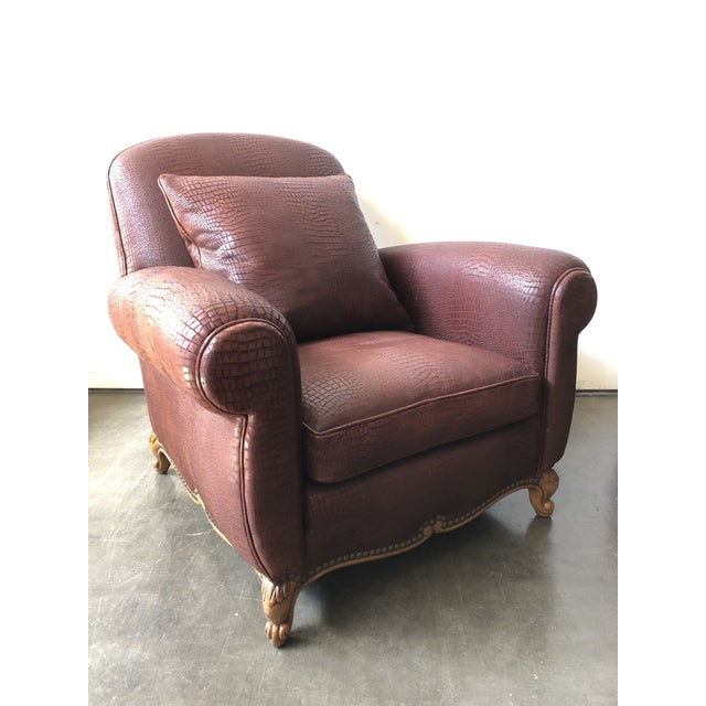 A substantial 1940s style club chair featuring rolled arms, hand-carved wooden scroll feet in a fruitwood finish, and...