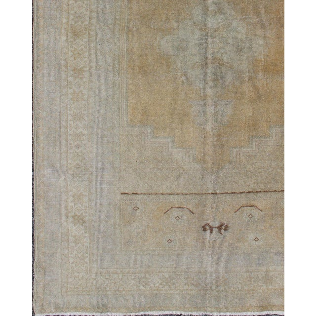This faded Oushak rug features an intricately beautiful design. The central medallion is complemented by a symmetrical set...