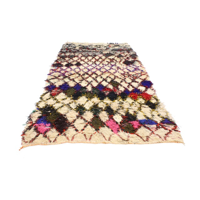 This is a vintage Berber Moroccan Boucherouite rug. The piece features an all-over diamond lozenge design, which holds...