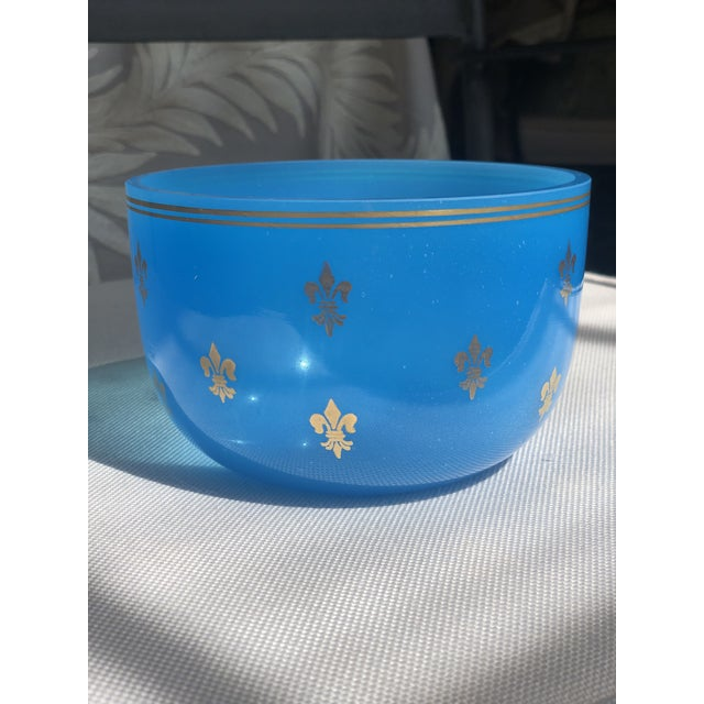 The deep blue color of this lovely opaline glass bowl is beautifully complimented by gilded trim and fleur-de-lis pattern
