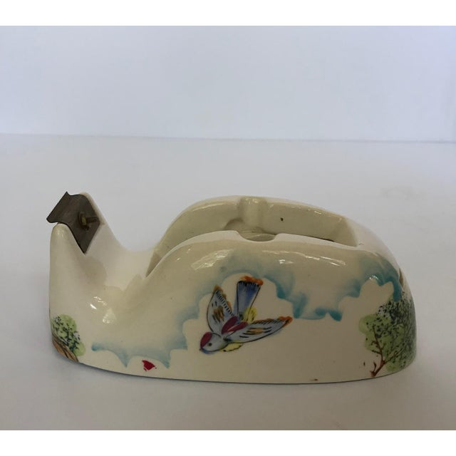 Vintage ceramic tape dispenser with hand painted whimsical outdoor scene with birds, clouds and trees. Tape cutter is...
