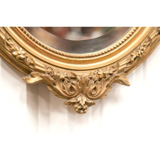 19th century French Louis XVI style hand-carved oval giltwood mirror, circa 1890. This beautiful Belle Époque period...