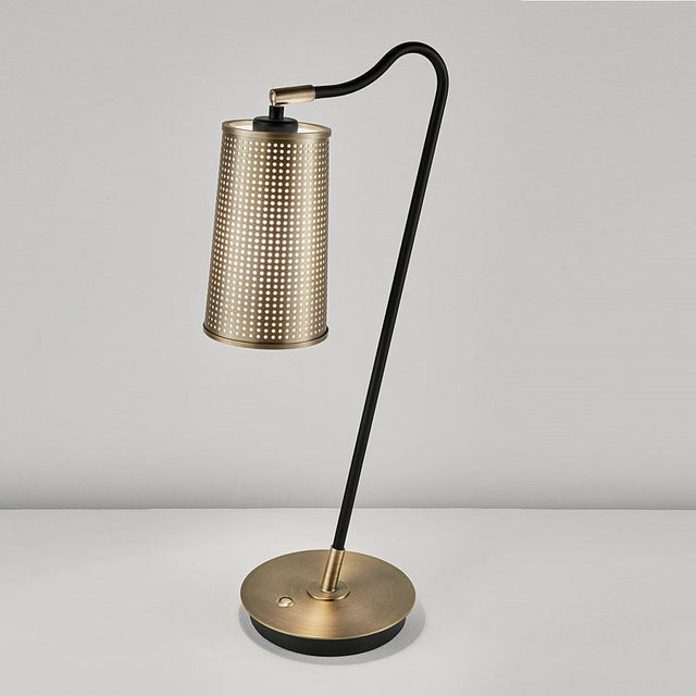 Golden bronze and satin black table lamp with a tapered perforted metal shade with an internal PVC opal diffuser to give a...