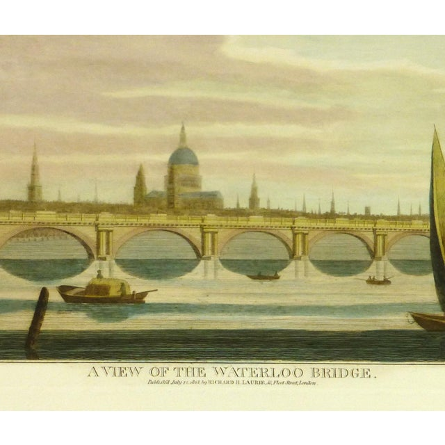 Hand-colored, later impression engraving featuring the Waterloo Bridge in London, with the city in the background. Modeled...