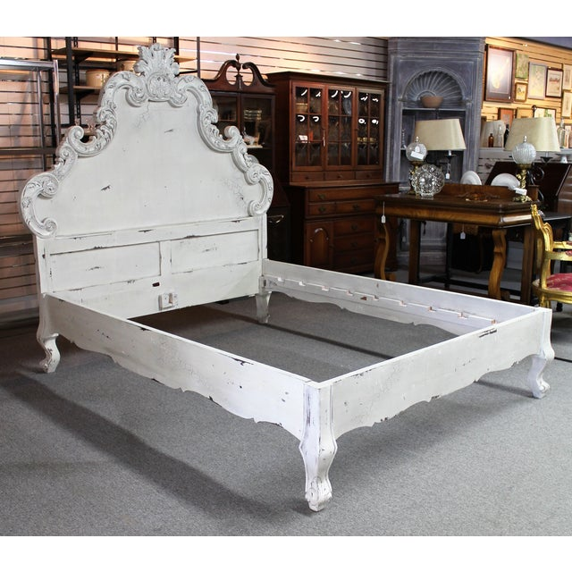 French Country carved queen-size bed frame featuring a distressed, white-painted finish. The piece is a floor model that...
