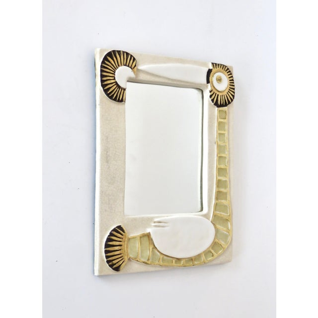 A French ceramic mirror by Francois Lembo with stylized bird motifs in gold and cream glaze, France, 1970s. In very good...