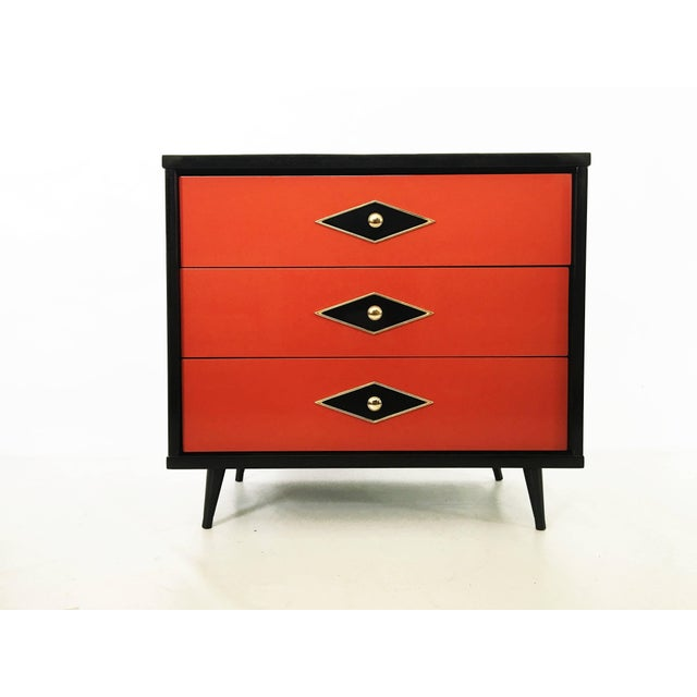 Stunning pair of neoclassical two-toned lacquered chest of drawers or commodes. With three drawers having a black with...