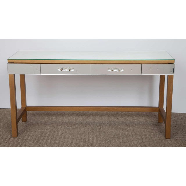 A chic mirrored console table with a giltwood base. The two drawers have pulls in Murano glass.