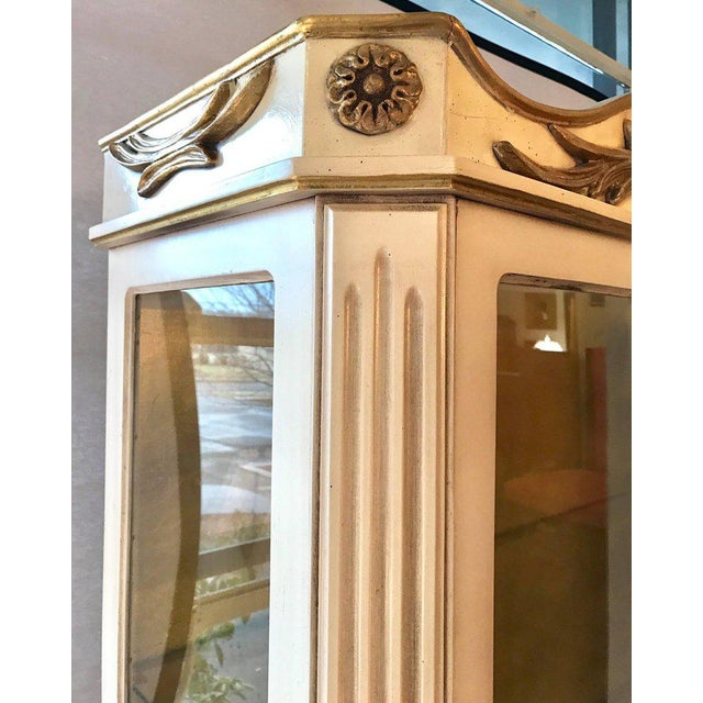 Stunning neoclassical style Italian cream painted 2 pc China cabinet with carved gold detail. Front door opens to glass...