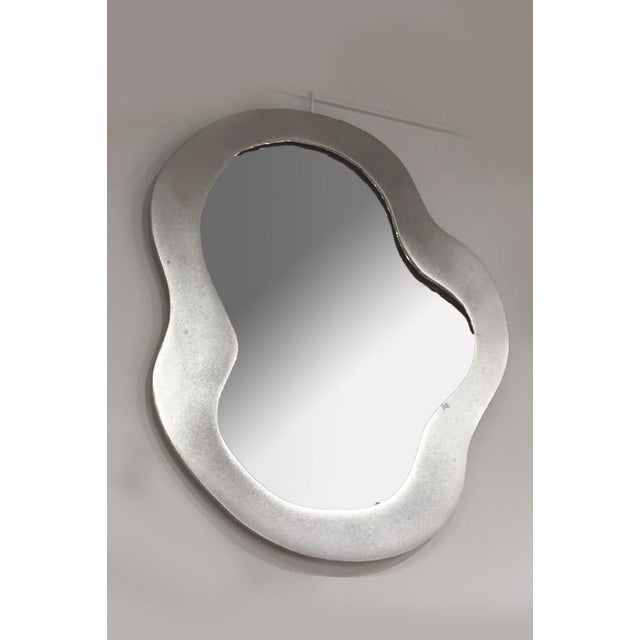 Cloud shape mirrored glass, encompassed by a broad frame of bronze with a silvery finish. The smaller version of Chauvet's...