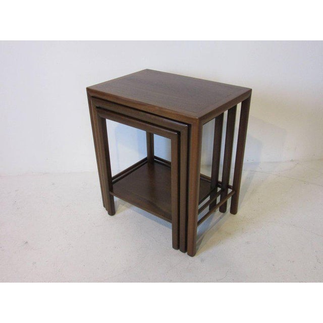 A set of three nesting tables with dark walnut frames and inserted rosewood table tops. The smallest table has a shelve to...
