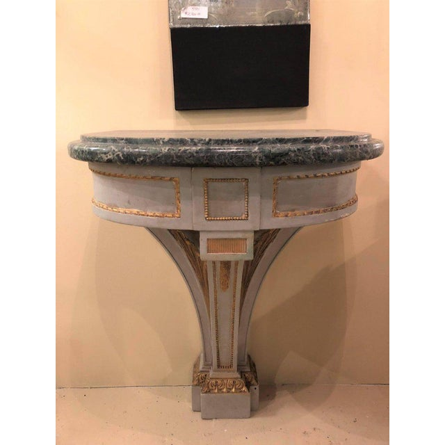 Pair of Hollywood Regency painted and marble demilune consoles. Each having a demilune form supporting a marble top....