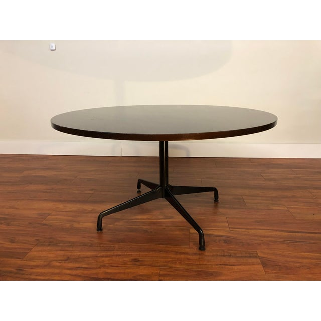 A circular conference or dining table by Ray and Charles Eames for Herman Miller in mahogany. This table features a...