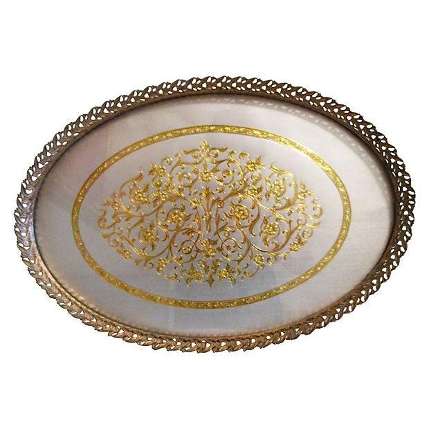 Lovely midcentury oval vanity tray featuring a matte-silver foil base with gold foil floral relief under glass. Gold-tone...