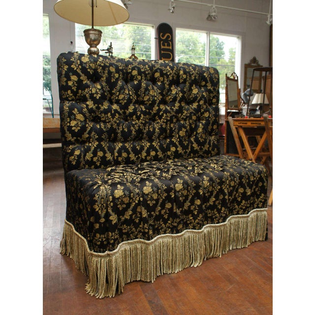 Victorian-style upholstered and tufted banquette with black and gold (yellow ochre) fabric and deep matching fringe....