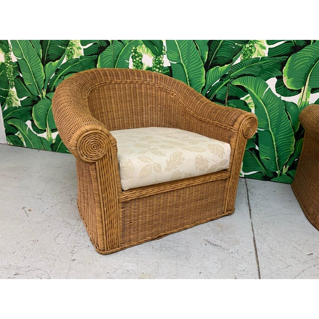Pair of vintage wicker club chairs in the manner of Michael Taylor feature sculptural design and neutral upholstery. Very...