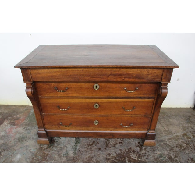 Made of solid walnut, this handsome commode features three drawers with brass swan neck handle pulls. Raised on bracket...