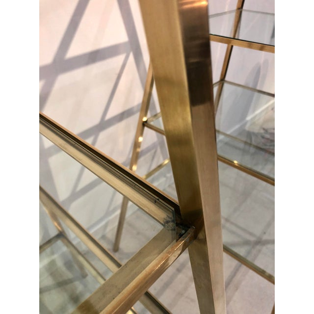 Pair of polished brass obelisk shaped etageres with glass shelves-- wonderful for displaying a collection or also striking...