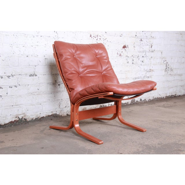 A sleek and stylish minimalist Scandinavian Modern bentwood teak and cognac leather lounge chair By Ingmar Relling for...