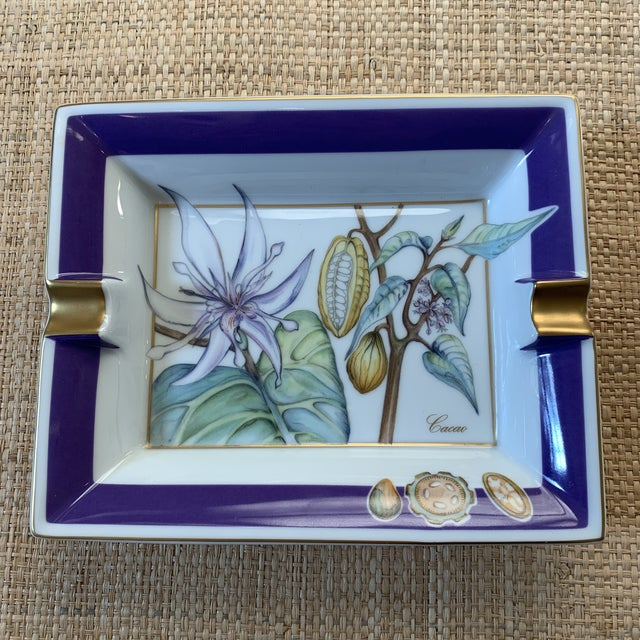 Hermes France porcelain ashtray. Features the cacao plant with greens and purple. 24k gold detailing. New condition.