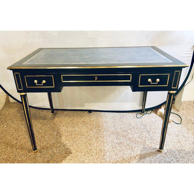 A Maison Jansen style Hollywood Regency bronze mounted writing table or office desk having a finely tooled leather top....