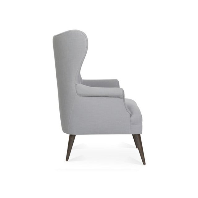 Midcentury inspired wingback chair with button tufts and tapered legs. Upholstered in Kim Salmela Ellie Nickel, a...