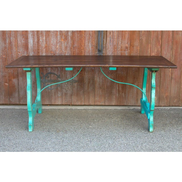 A charming 17th Century style dining table with an aged oak top standing on beautifully painted turquoise Spanish Lyra...