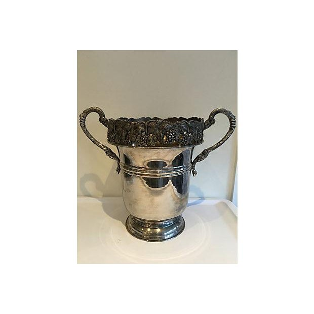 A handled silver-plate champagne or wine bucket. This piece is ornately decorated with grapevines design. No marks.