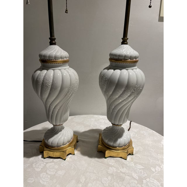 Pair of French porcelain white table lamps. Lamps are decorated with a white overlay with a floral design. Made in the...