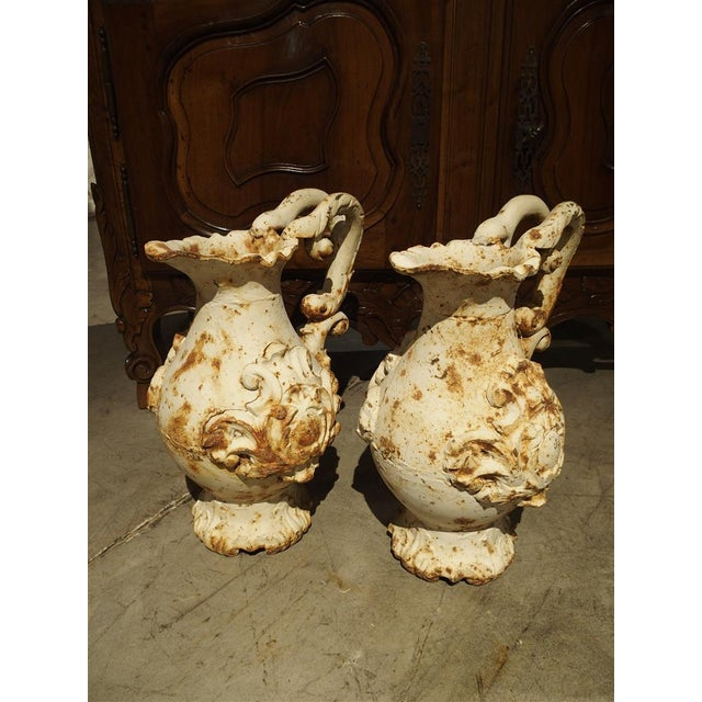 This pair of large antique French parcel paint pitchers has very ornate designs. In the Rococo style, their motifs are...