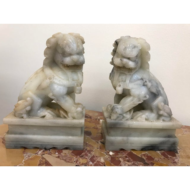 A pair of Chinese export carved marble foo lions from the late 19th century to early 20th century.