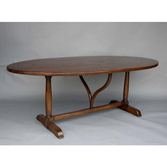 Custom oval walnut wine tasting dining table with wishbone shaped support and column trestle base. Shown here in walnut...