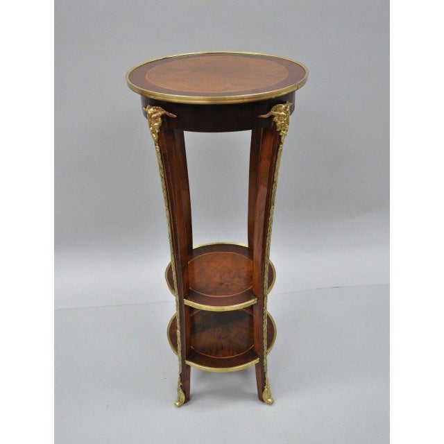 Reproduction Regency style, bronze rams heads and ormolu, 3 tiers with burl wood and inlay, impressive form. Made in the...