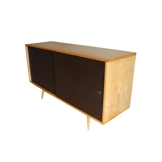 This Paul McCobb sideboard is made of solid maple wood. The sliding doors are brown in color with a grass like texture...