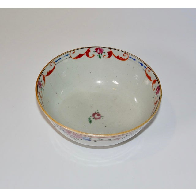 This is a 19th century Chinese export bowl in white. It has a decorative floral design in pinks, reds, and blues around...