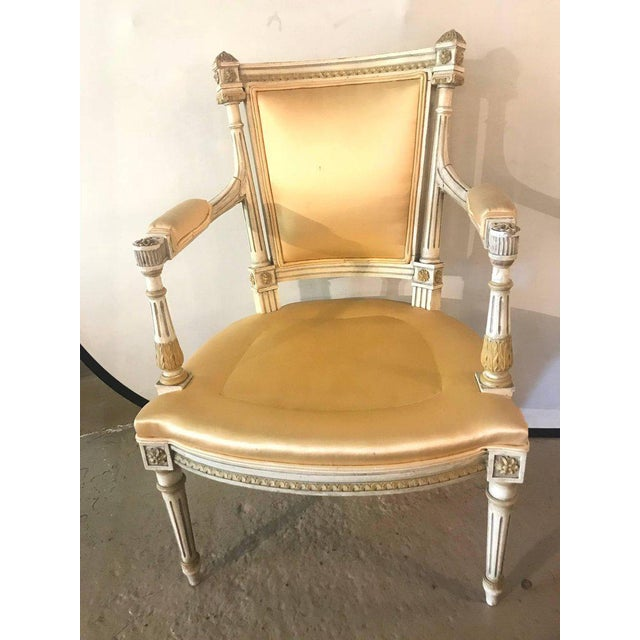 A Jansen parcel paint and gilt decorated arm or desk chair in what appears to be a silk upholstery.