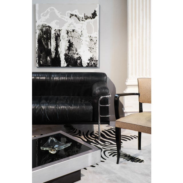 Circa 1960, vintage Bauhaus style sofa in black leather and chrome, in the style of Le Corbusier's LC2 sofa and armchairs.