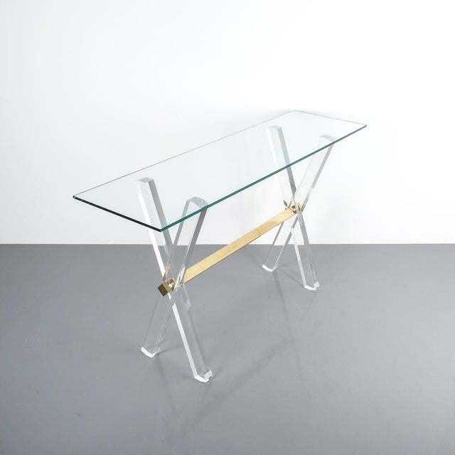 Lucite and Brass X Frame Console Table, Circa 1970.Elegant console table consisting of a lucite X frame with a horizontal...